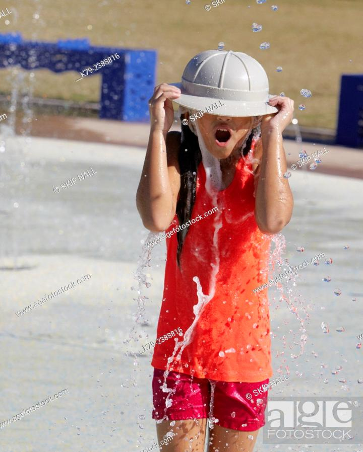 Stock Photo: A little girl playing in the water at a water park.
