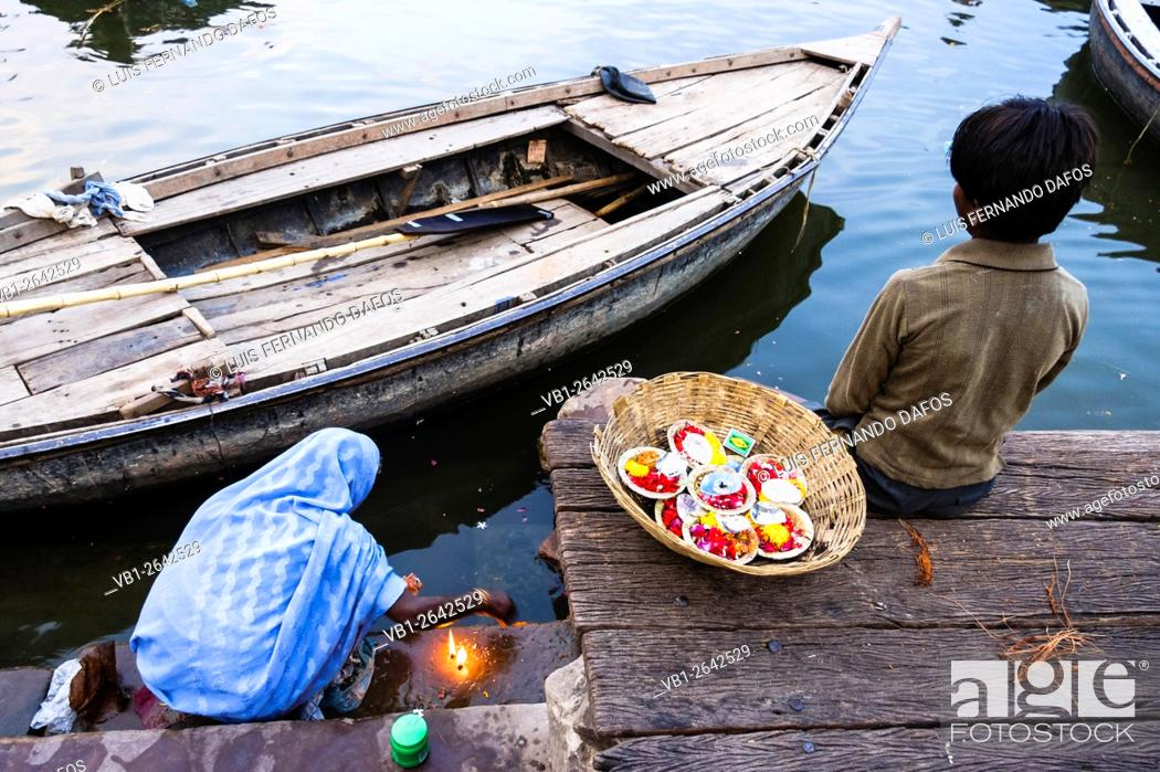 Imagen: Old lady and child lighting puja candles by Ganges river, Varanasi, India.