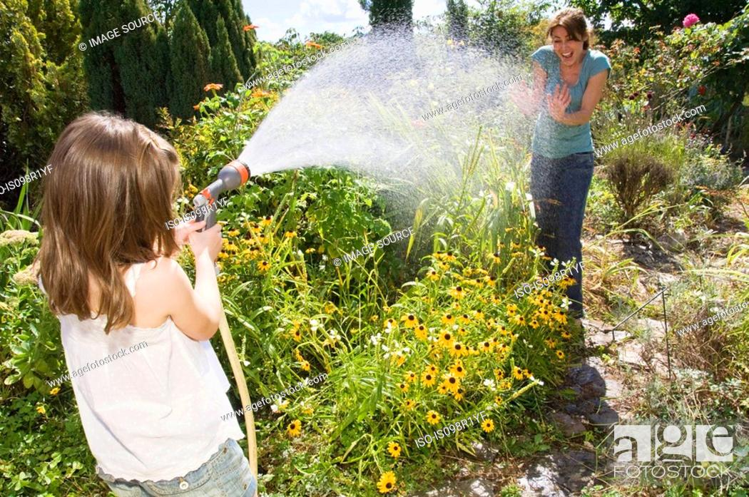 Stock Photo: Girl spraying water at mother.