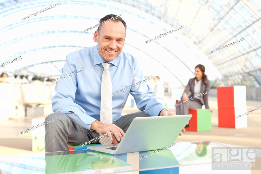 Stock Photo: Germany, Leipzig, Businessman using laptop with business people in background.