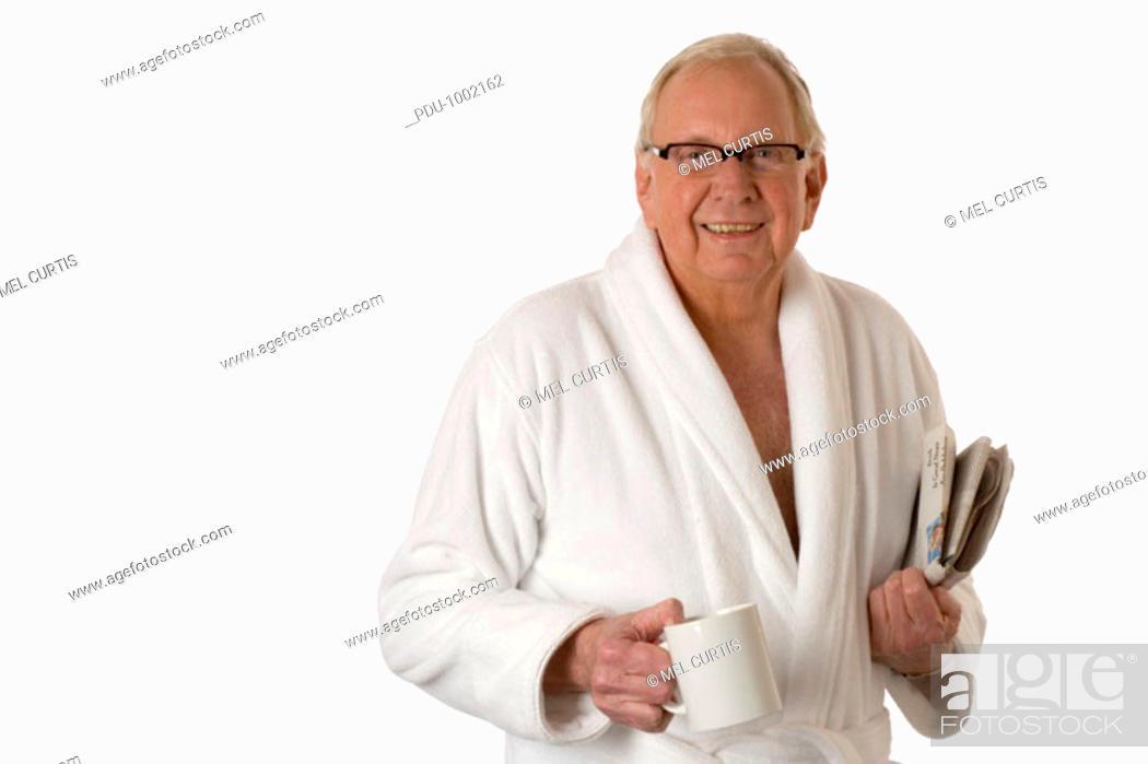 Stock Photo: Senior man wearing bathrobe, carrying newspaper and coffee, portrait.