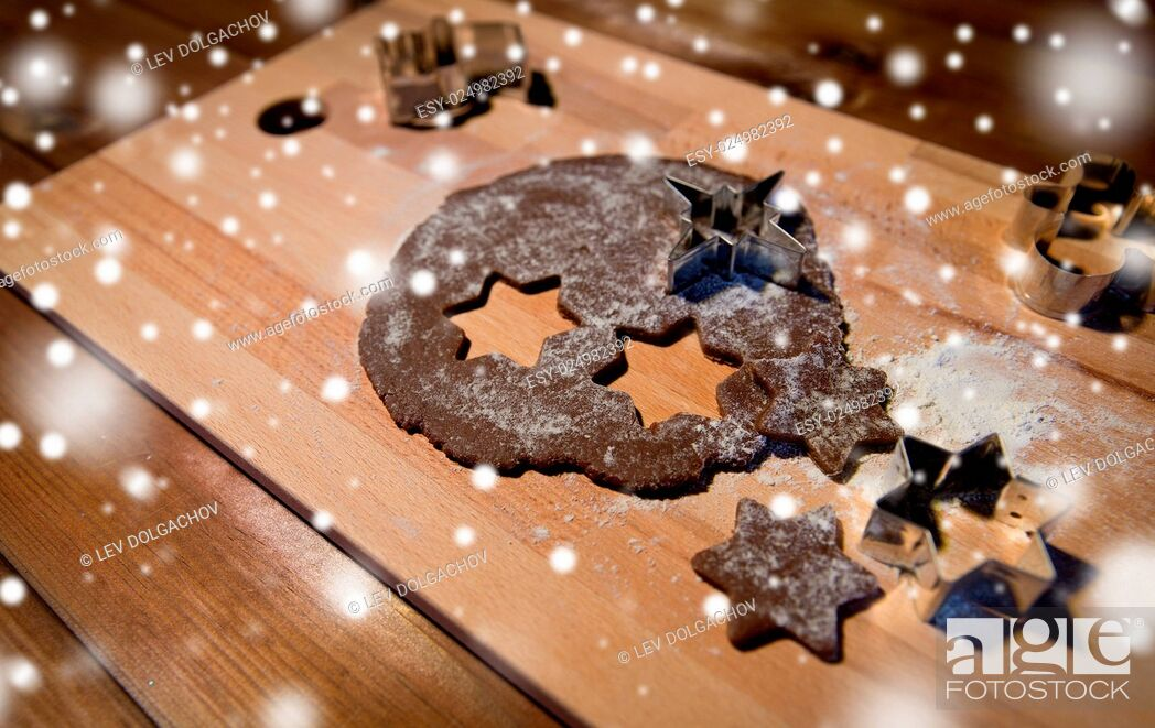 Stock Photo: baking, cooking, christmas and food concept - close up of gingerbread dough, molds and flour on wooden cutting board from top.