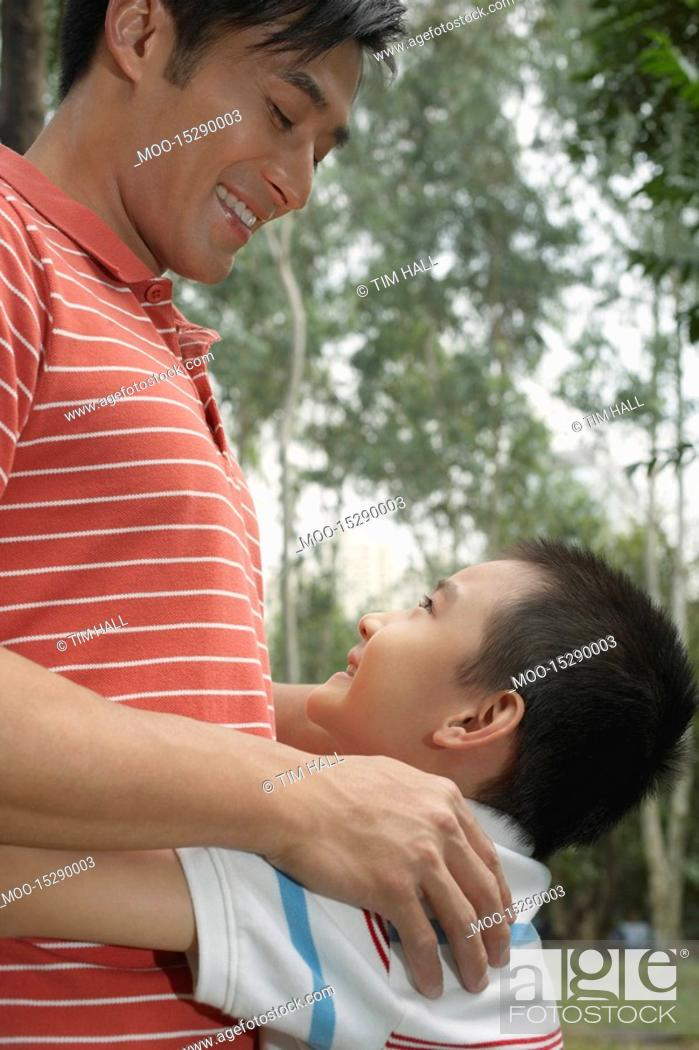 Stock Photo: Father and son 7-9 in park embracing and looking in eyes.