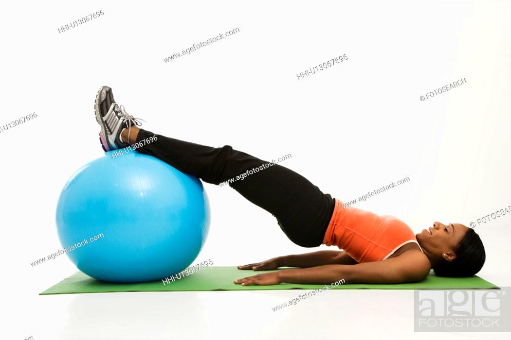 Stock Photo: Profile of African American woman stretching on mat with legs on exercise ball.