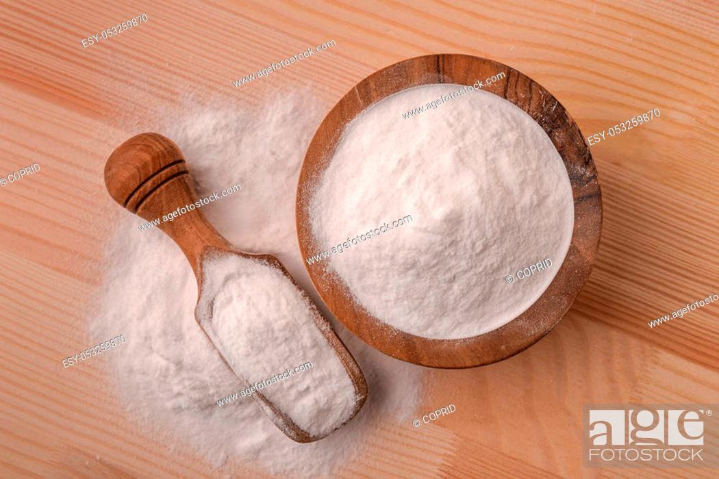 Stock Photo: Top view of bowl and scoop with baking soda on wooden table.