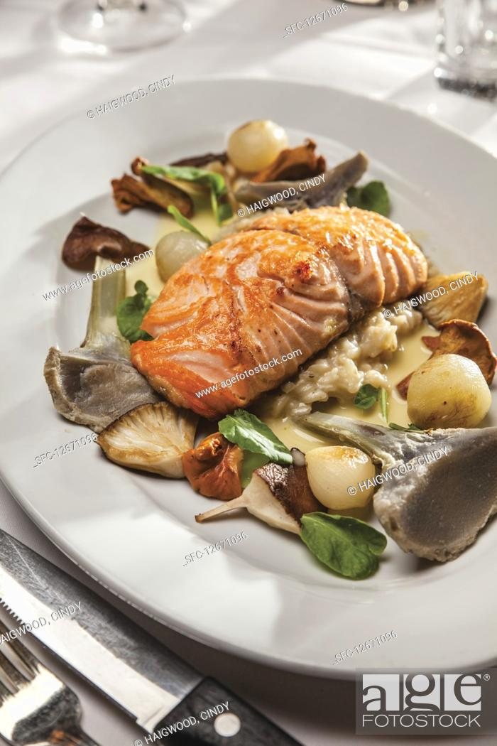 Stock Photo: Wild salmon with mushroom risotto, chantarelles, shitake, artichoke hearts and glazed pearl onions.