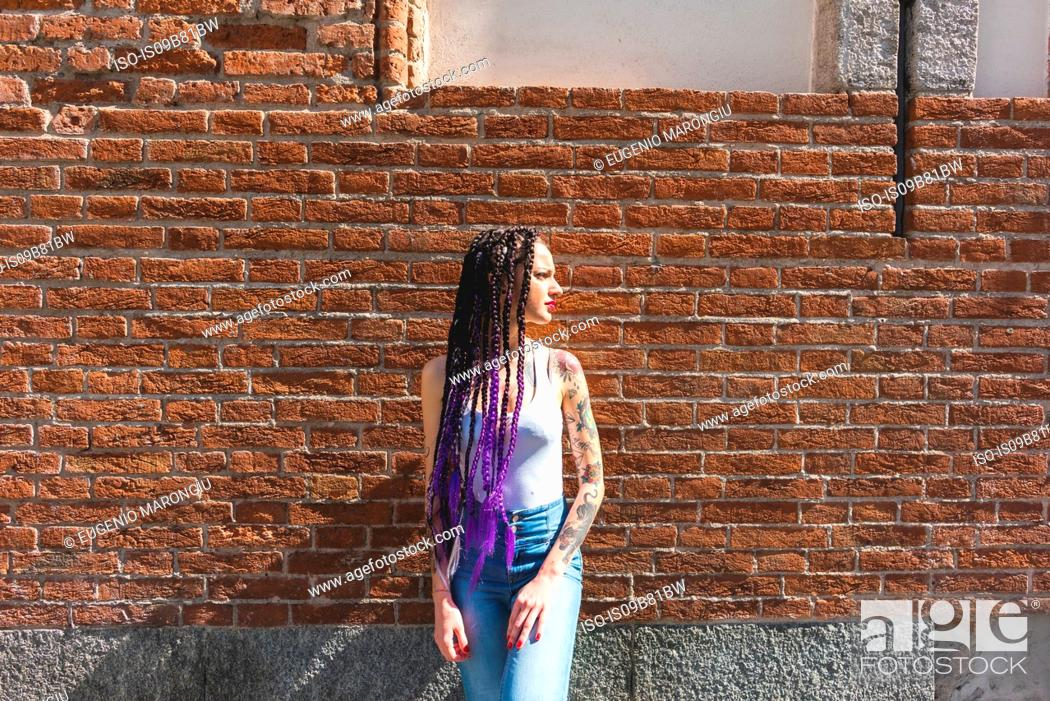 Stock Photo: Woman standing next to red brickwall.