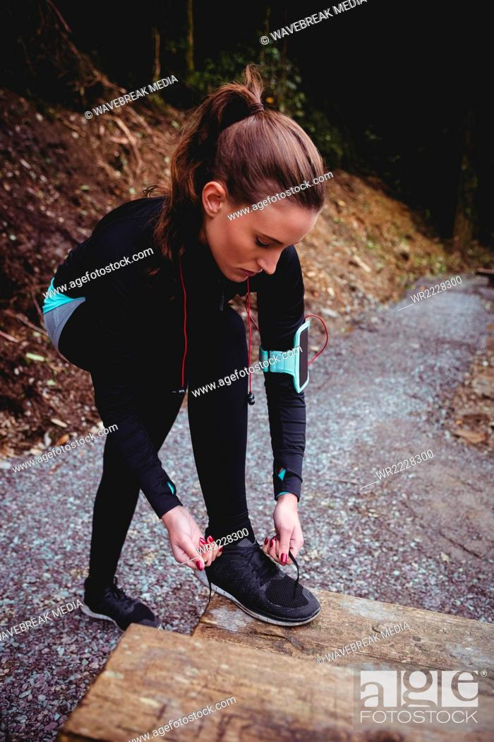 Stock Photo: Fit brunette with armband tying her shoe lace.