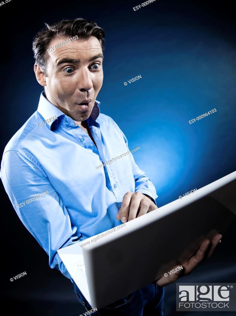 Stock Photo: caucasian man internet surfing amazed portrait isolated studio on black background.