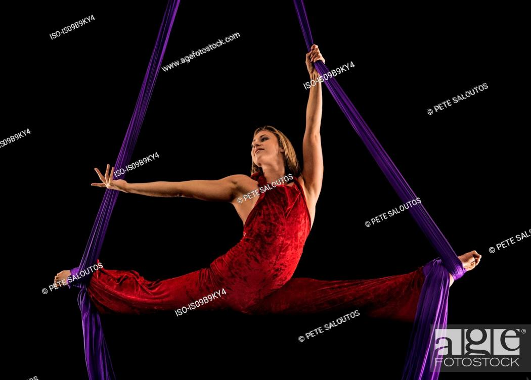 Stock Photo: Young female aerial acrobat doing the splits with feet wrapped in silk rope against black background.