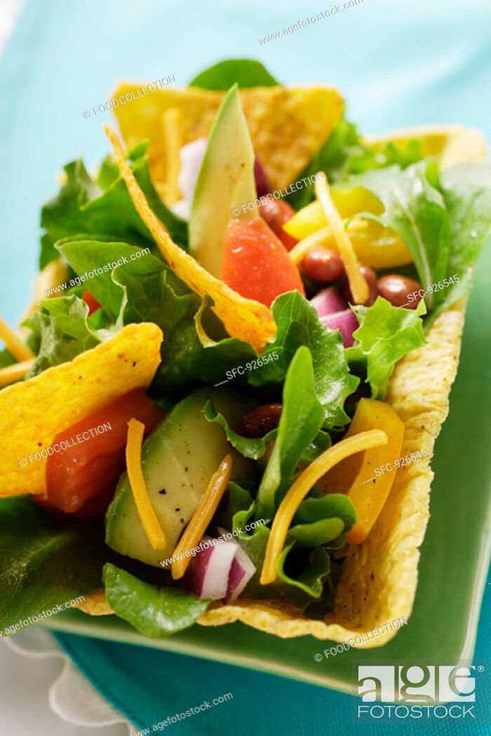 Stock Photo: Mexican salad with vegetables and taco chips in taco shell.