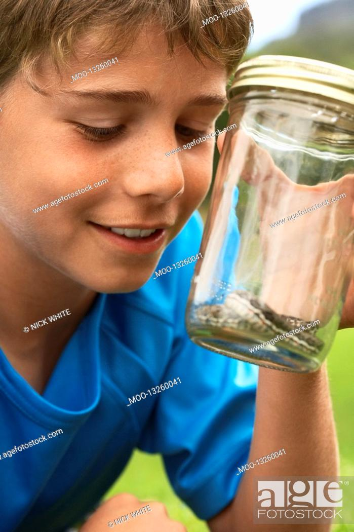 Stock Photo: Boy Looking at Snake in Jar.