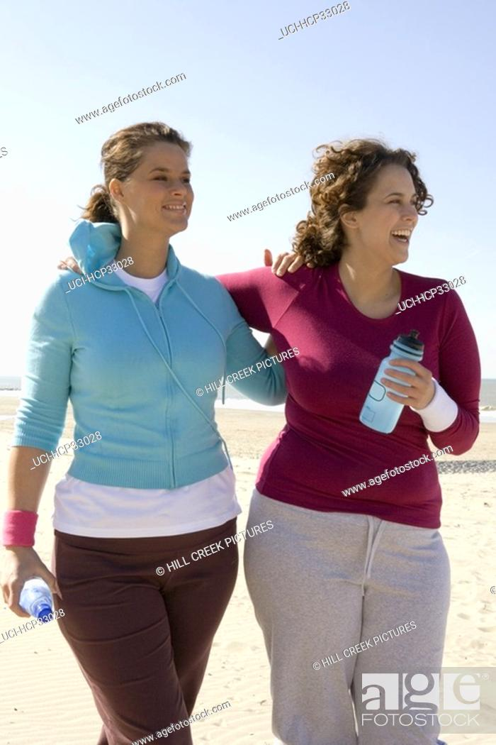 Stock Photo: Two women walking arm in arm at beach.