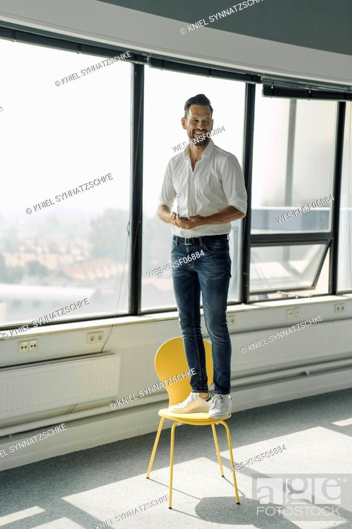 Stock Photo: Happy mature businessman standing on yellow chair in empty office.