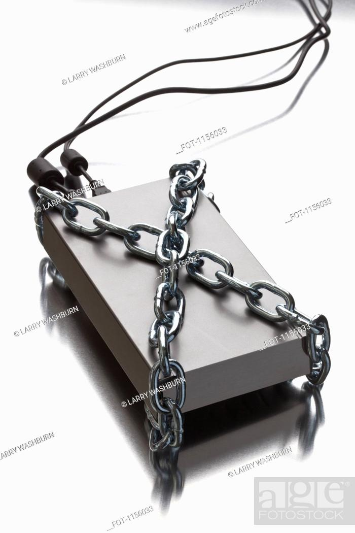 Stock Photo: A thick metal chain wrapped around an external hard drive.