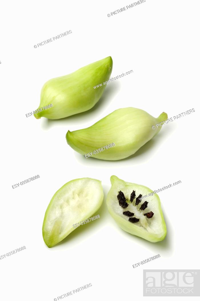 Photo de stock: Whole and half green heirloom wild cucumber with black seeds on white background.