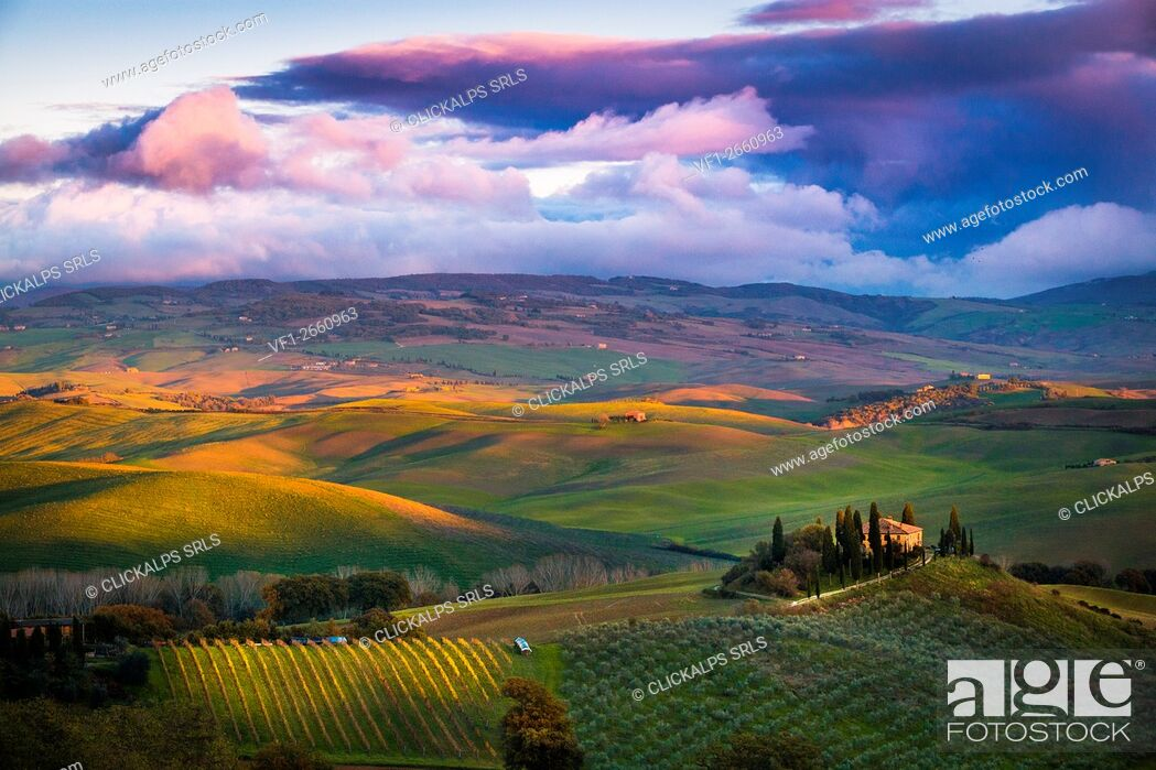 Stock Photo: San Quirico d'Orcia, Tuscany, Italy. Sunset over the valley with some farmhouses and a very cloudy sky.