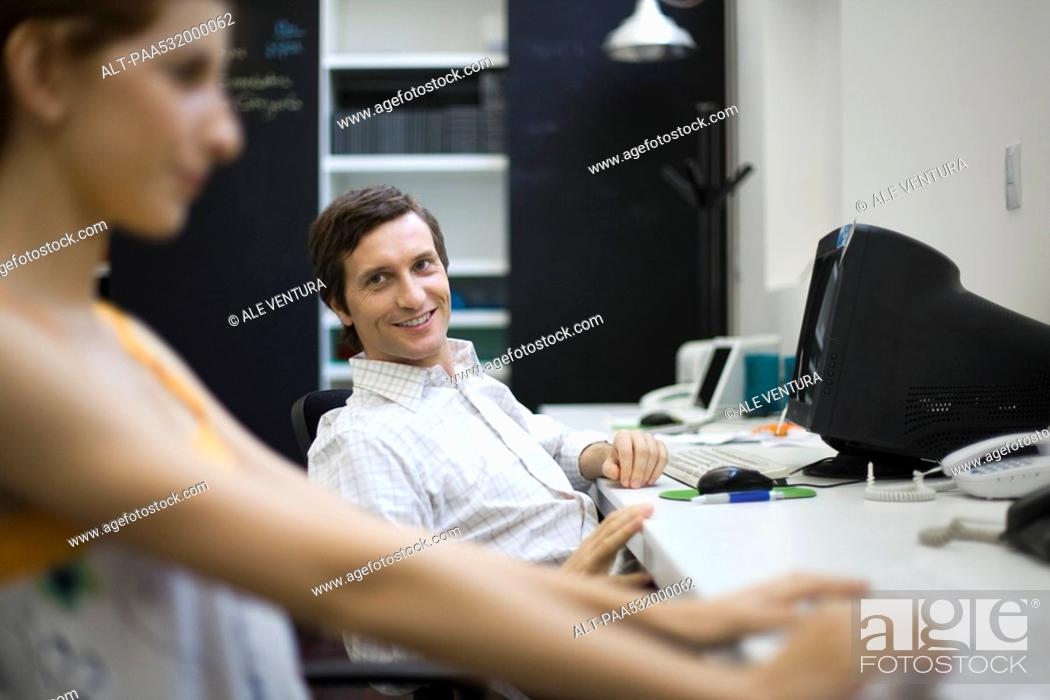 Stock Photo: Man sitting at desk, smiling at female colleague.