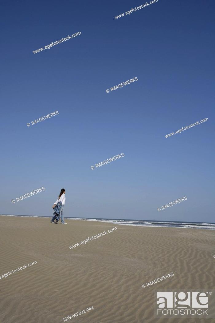 Stock Photo: Rear view of a young woman walking on sand near the shore.