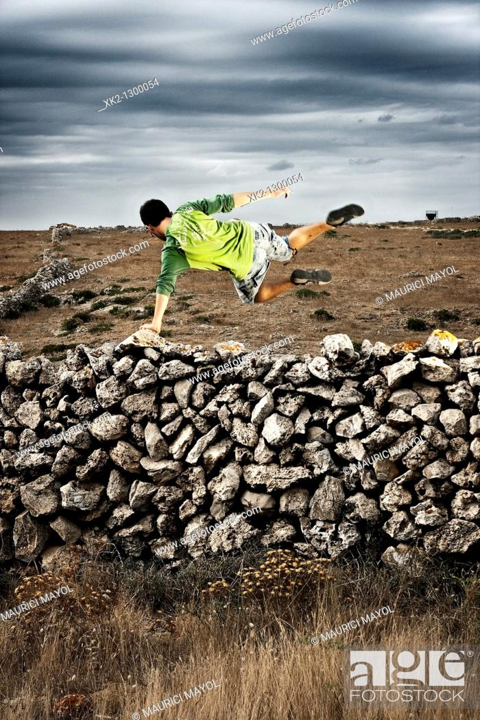 Stock Photo: Young man jumping over dry stone wall. Minorca, Balearic Islansd, Spain.