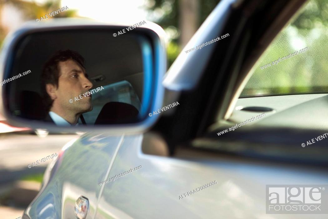 Stock Photo: Reflection of car driver seen in side-view mirror.