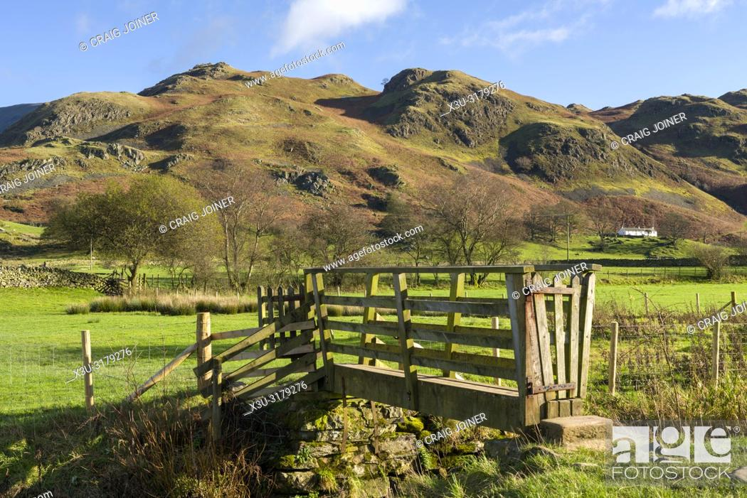 Stock Photo: A wooden footbridge over a small beck at Dale Bottom with High Rigg beyond in the English Lake District National Park, Cumbria, England.