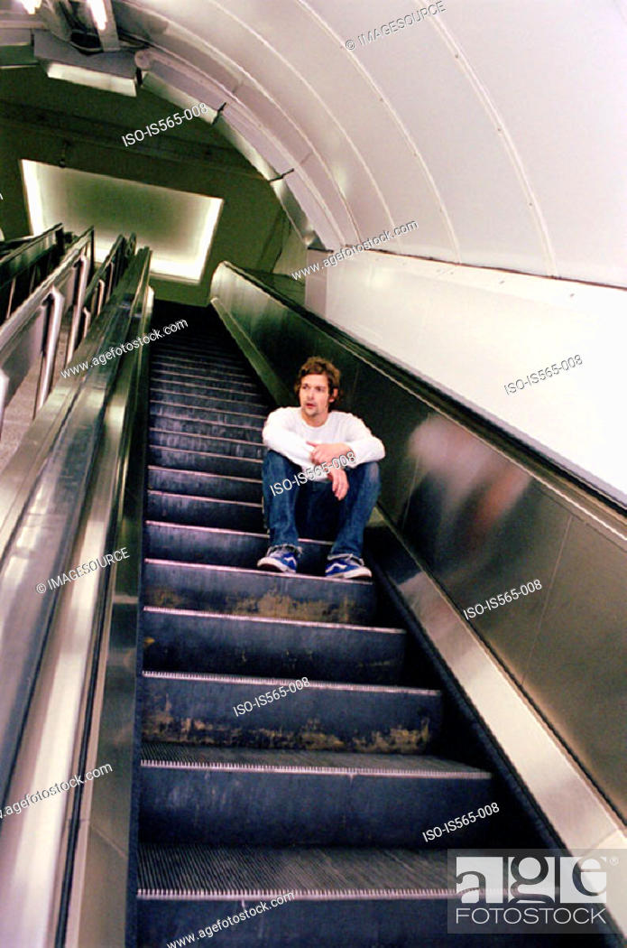 Stock Photo: Man sitting on escalator.