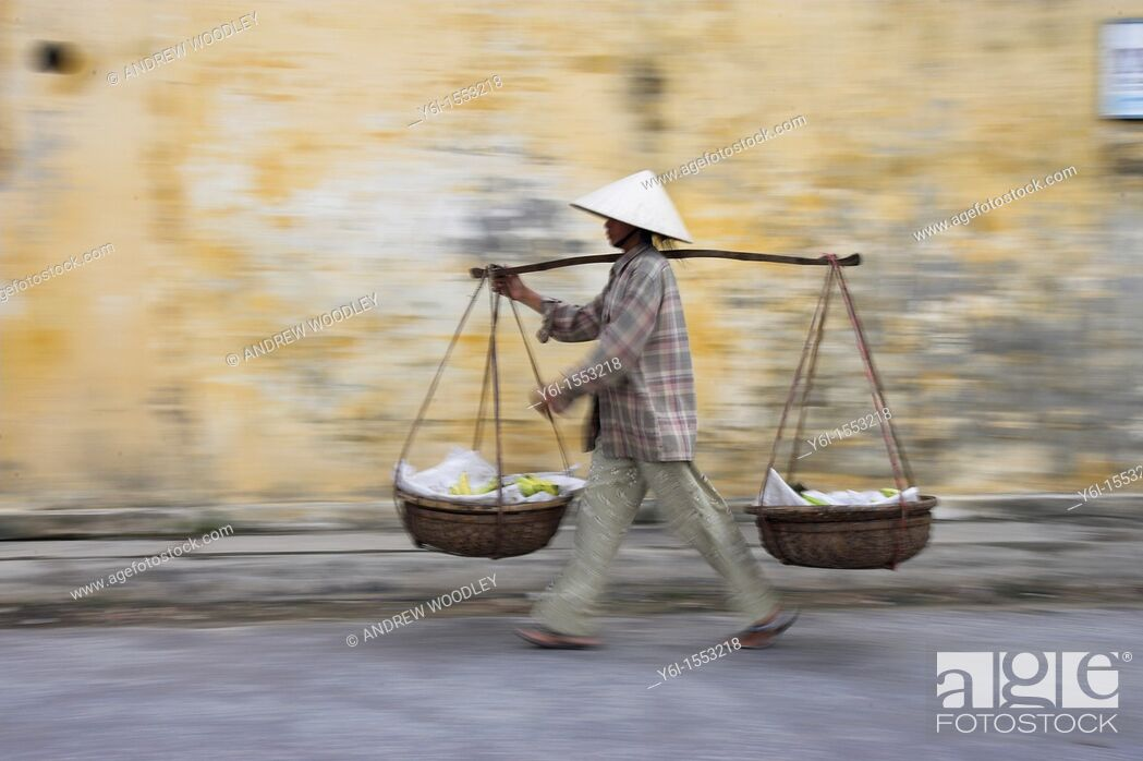 Stock Photo: Conical hat woman with banana baskets walks from market Hoi An historic town mid Vietnam.