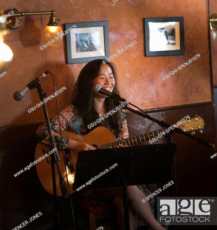 Stock Photo: Teen Girl Playing Acoustic Guitar at Cafe.