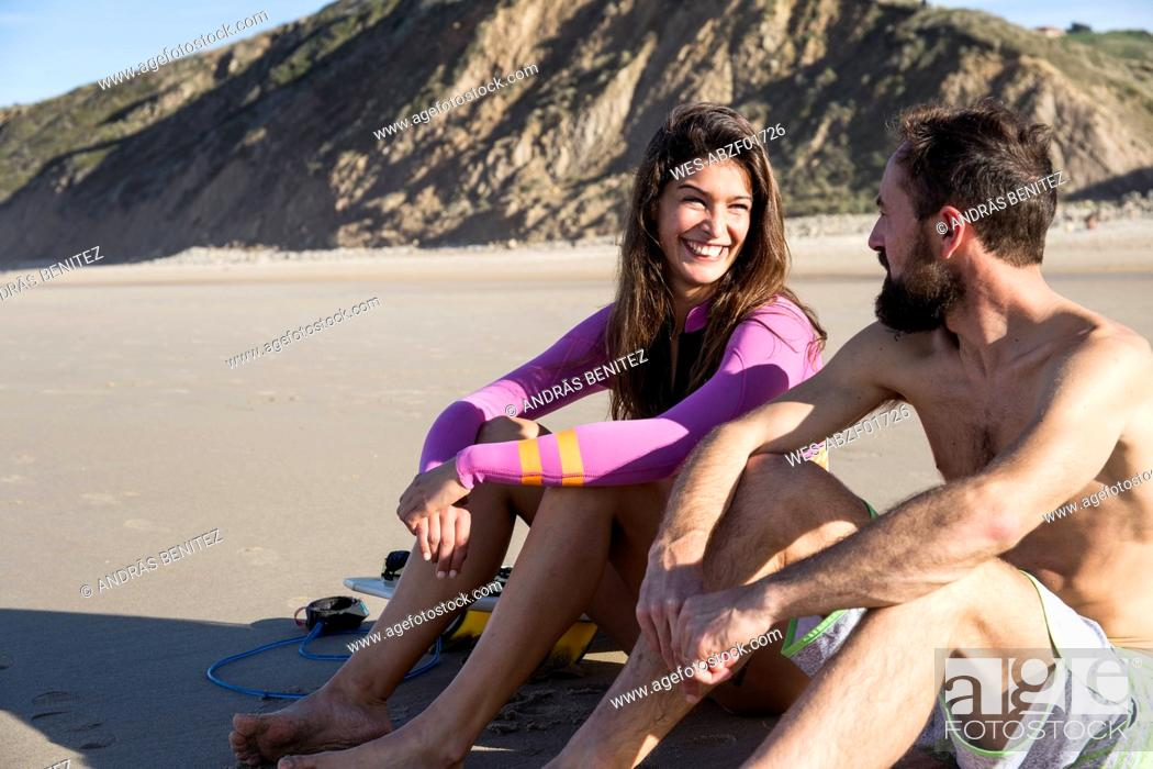 Stock Photo: Smiling couple with surfboard sitting on the beach.