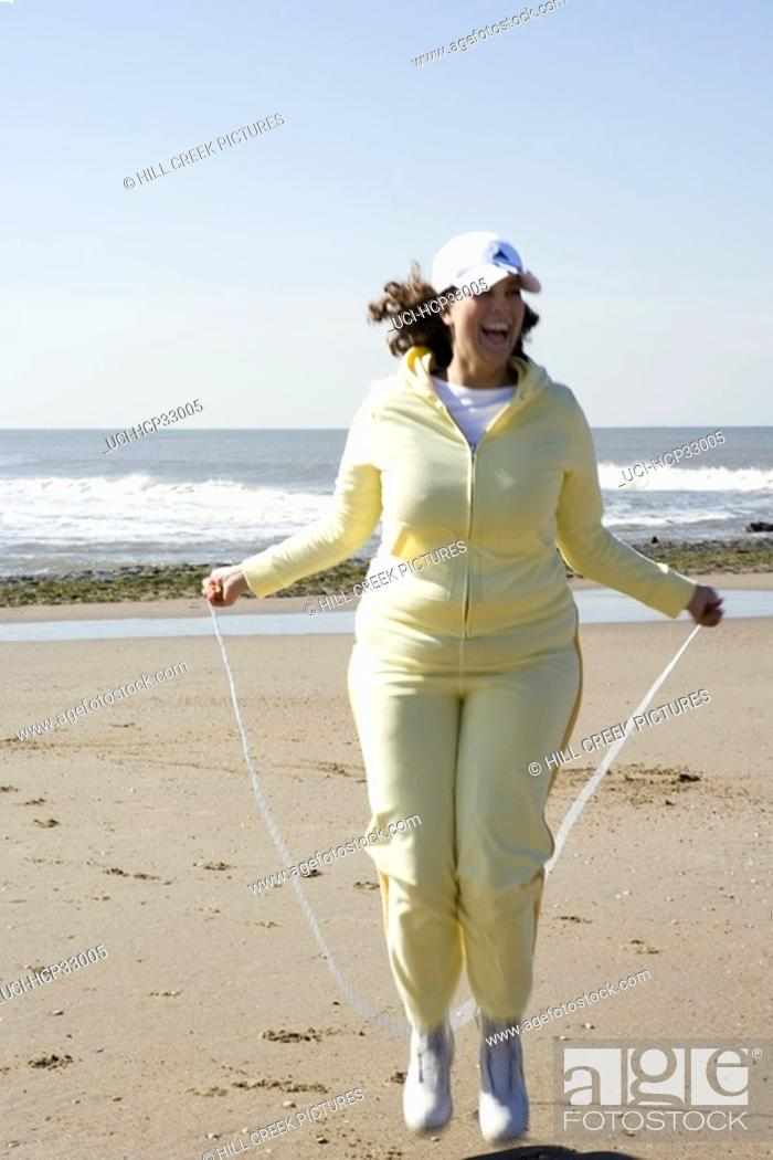 Stock Photo: Woman jumping rope on beach.