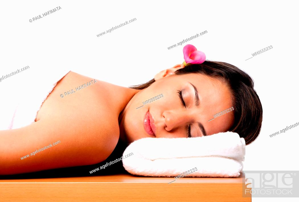 Imagen: Beautiful happy peaceful sleeping woman at a spa, laying on wooden massage table with head on pillow wearing a towel and pink Calla Lilly flower in hair.