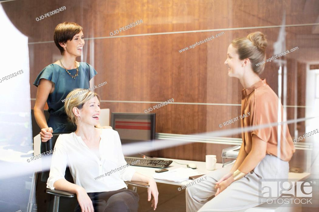 Stock Photo: Businesswomen laughing in office.