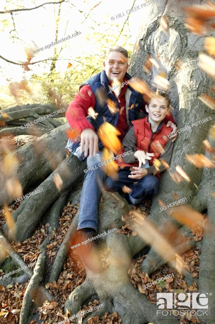 Stock Photo: Father and son throwing leaves.