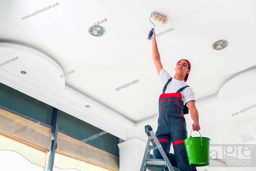 Stock Photo: Young painter painting the ceiling in construction concept.