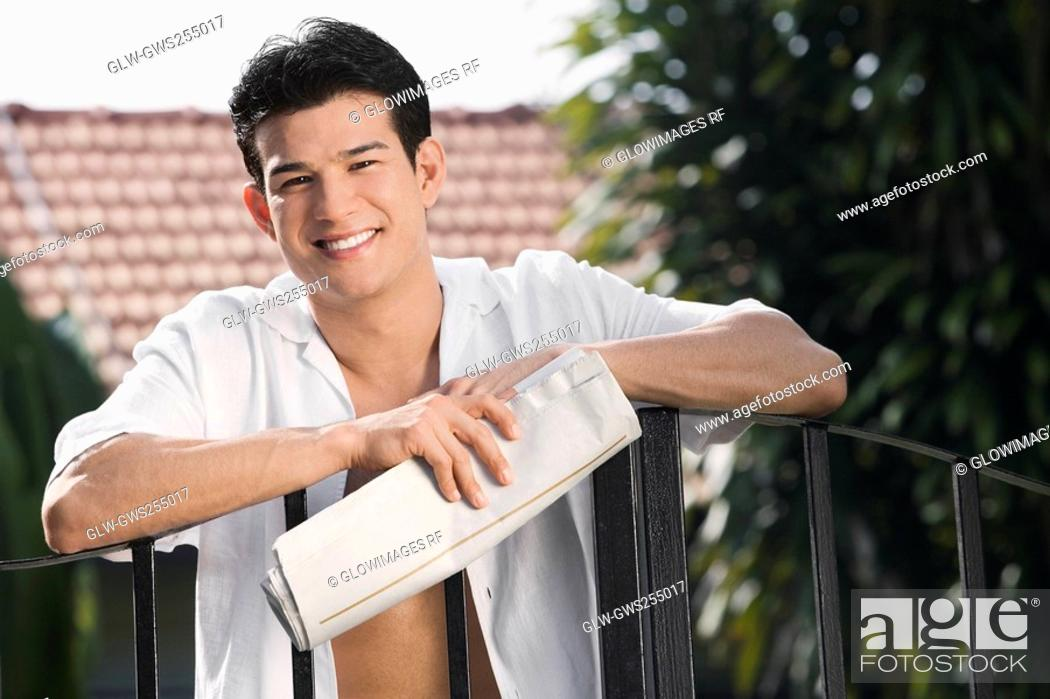 Stock Photo: Young man holding a newspaper and smiling.