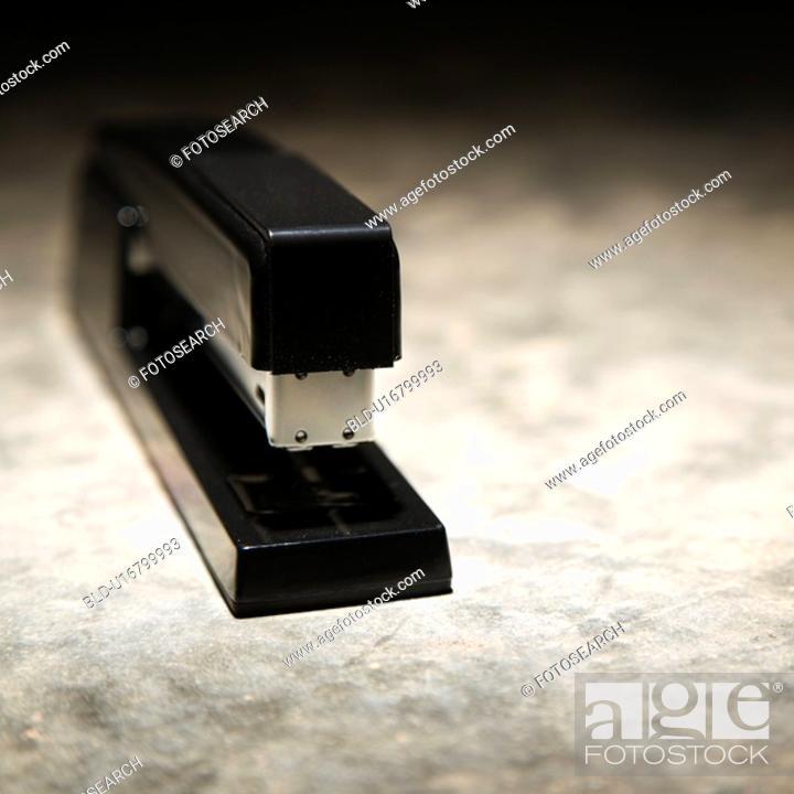 Stock Photo: Black stapler on textured background.