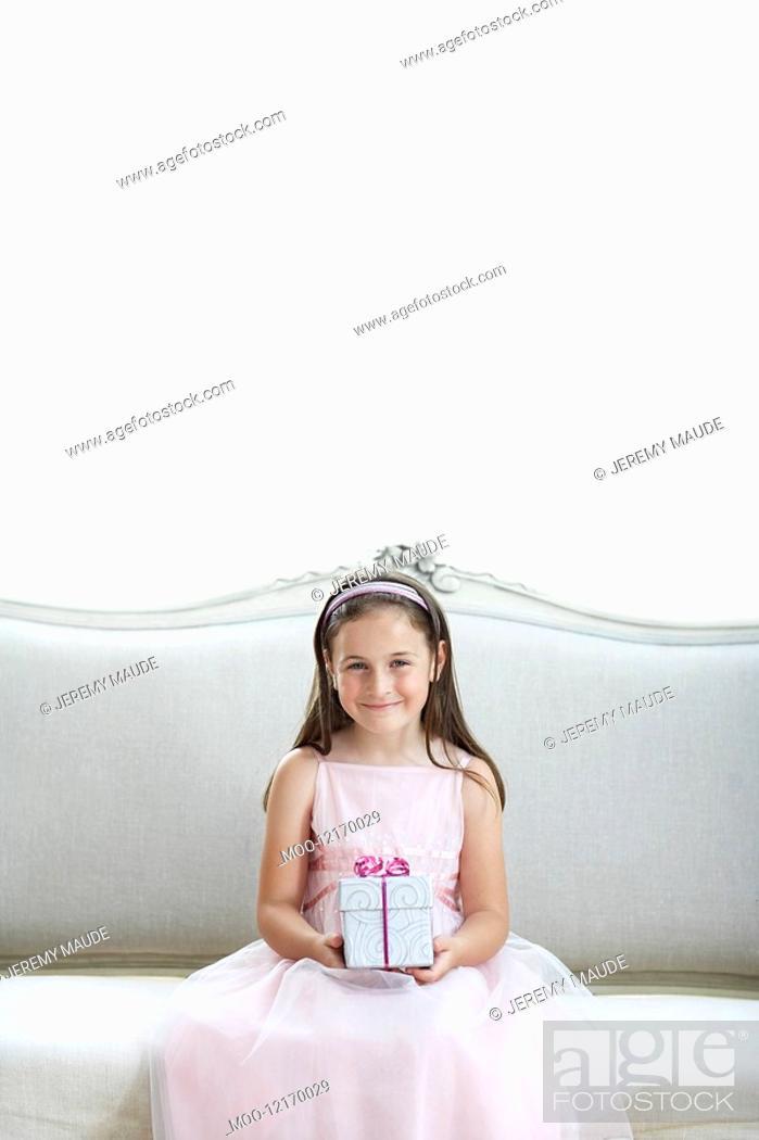 Stock Photo: Smiling girl in tutu sitting on sofa holding gift portrait.