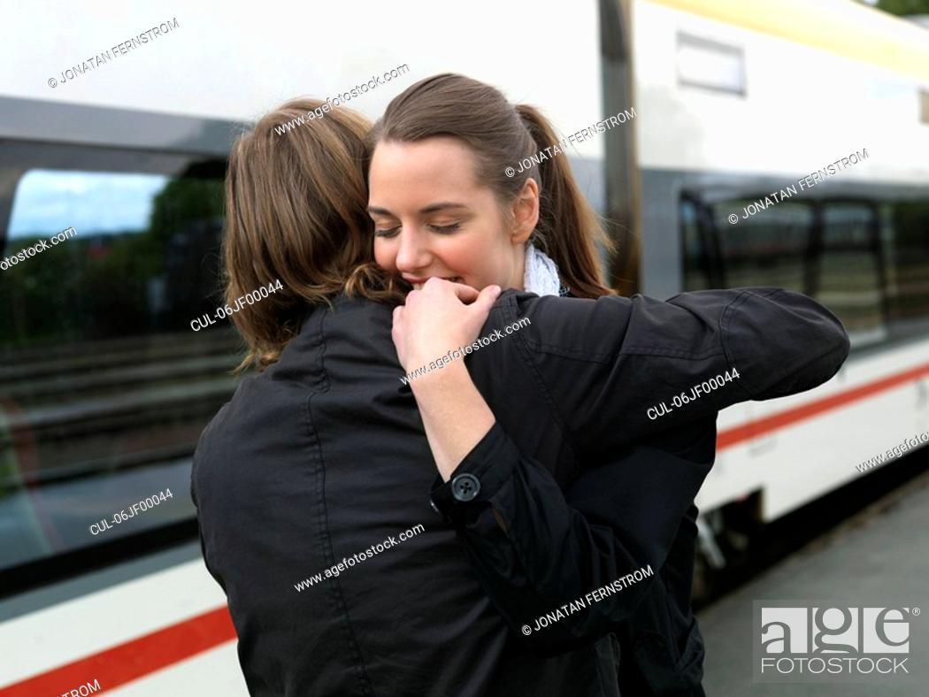 Stock Photo: Couple embracing on train station.