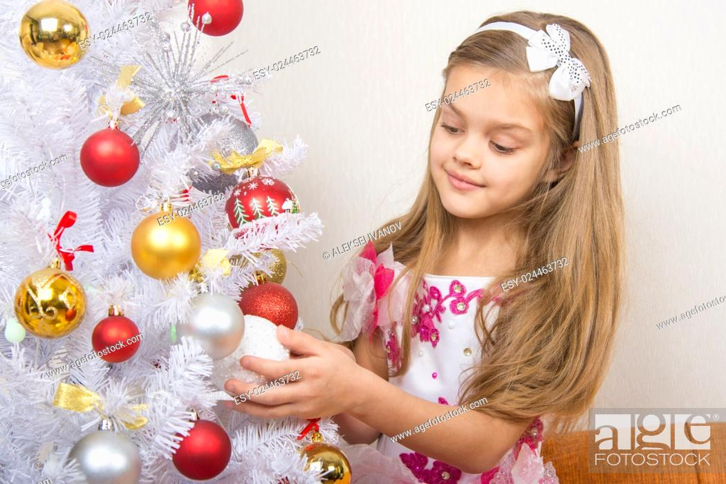 Stock Photo: Seven-year girl in a beautiful dress treats Christmas toys.