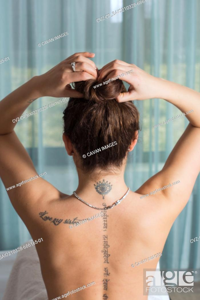 Stock Photo: Young woman gathers her hair on top of her head and prepares for.