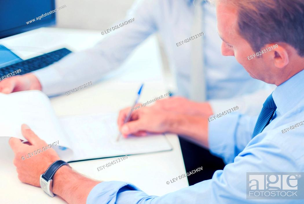 Stock Photo: businesss and office concept - businessmen with notebook discussing graphs on meeting.