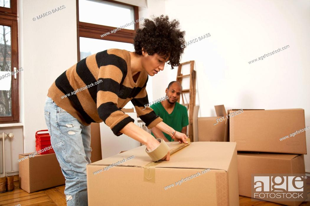 Stock Photo: A woman taping a moving box while a man watches.