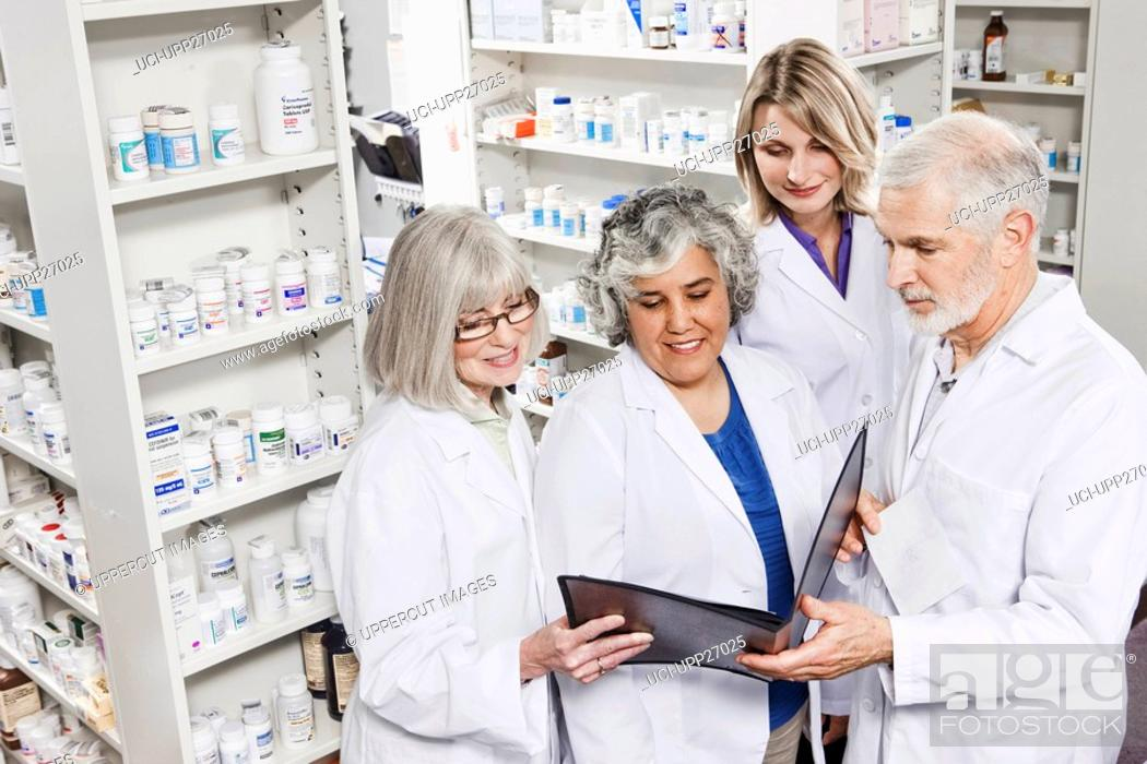 Stock Photo: Pharmacists reading file together.