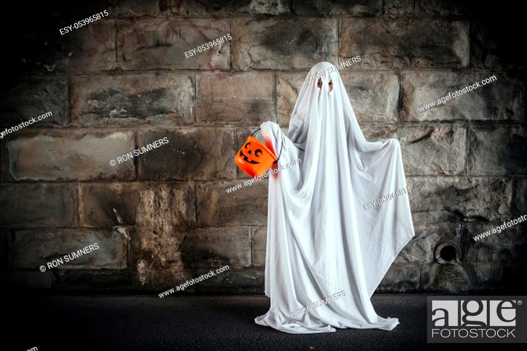 Stock Photo: Young boy dressed in a bed sheet to be a ghost, and holding a pumpkin pail for halloween.