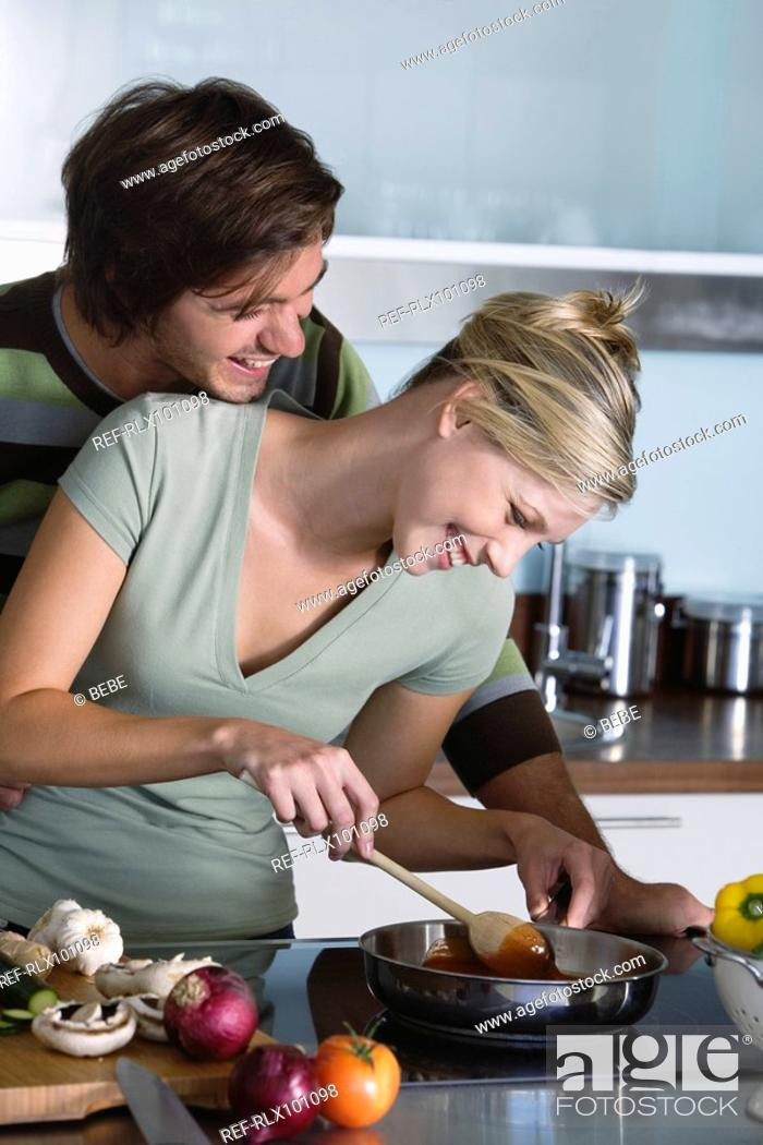 Stock Photo: Young couple in kitchen, cooking together, making pasta sauce, hugging, smiling.