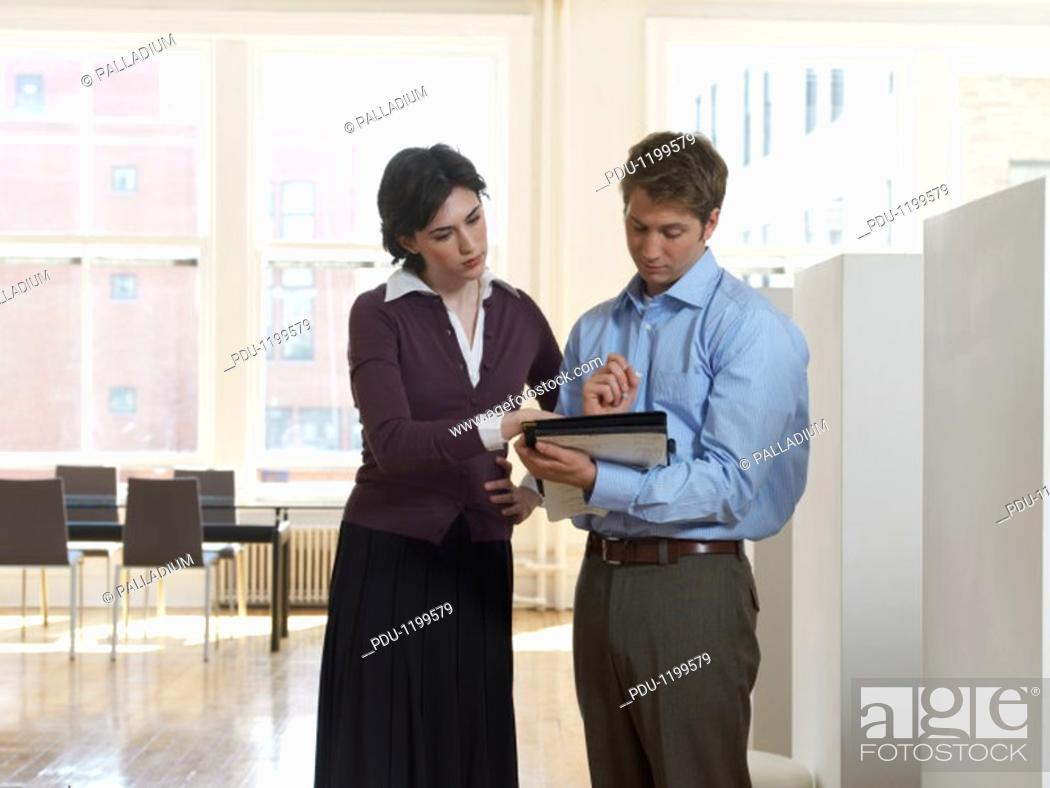 Stock Photo: Businessman and Businesswoman Examining a Document in a Folder.