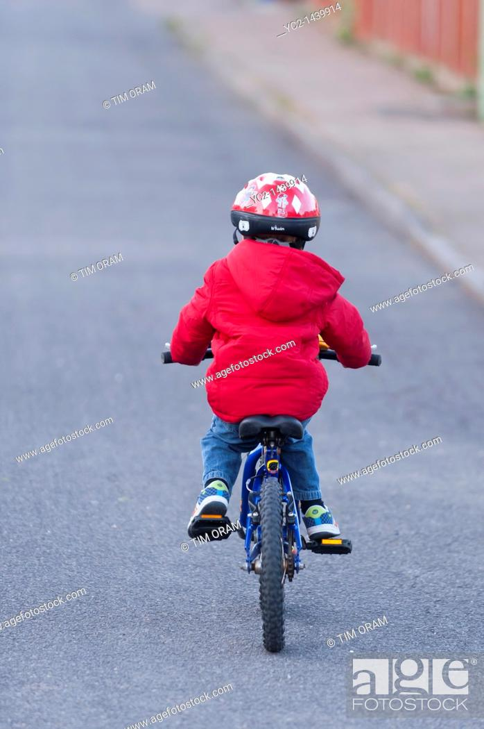 Stock Photo: A three year old boy riding his bike on the first day with no stabilizers in the Uk.