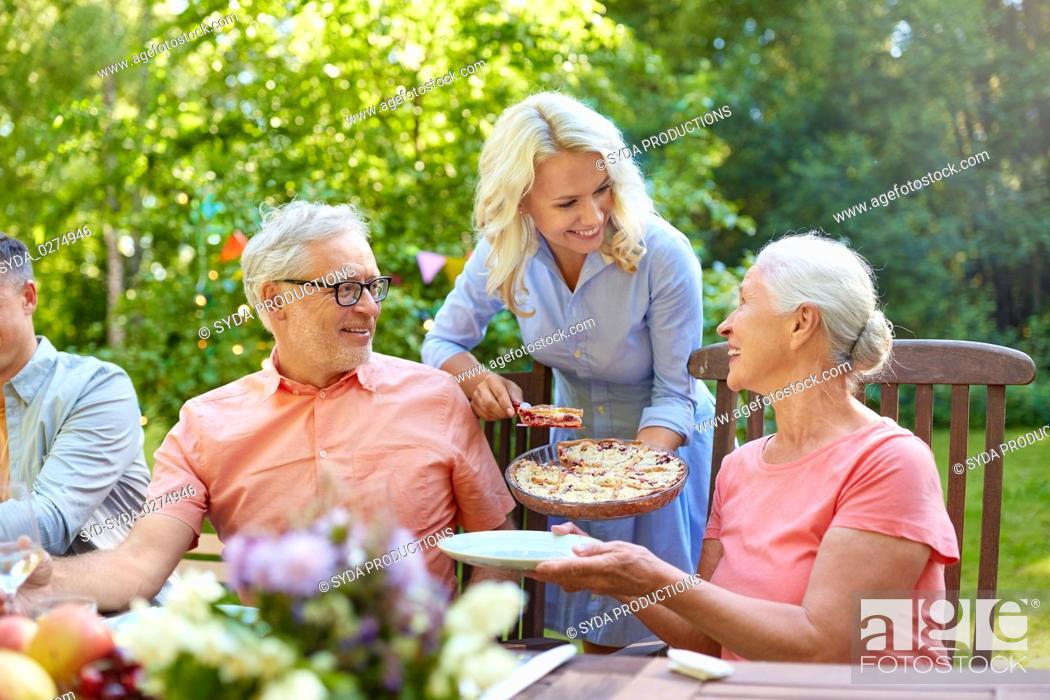 Imagen: happy family having dinner or summer garden party.