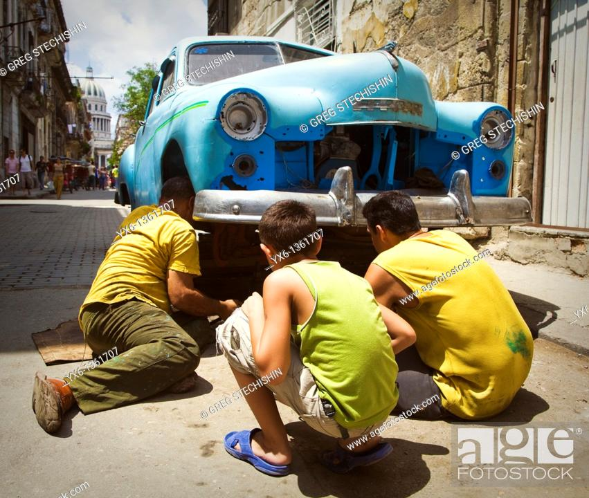 Stock Photo: Man man repairs a broken down car in the street while another man and a boy look on in Havana, Cuba.